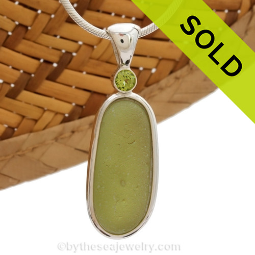 This beautiful bubbled Peridot Green Seaham sea glass piece is set in our Deluxe Wire Bezel© pendant setting. This incorporates a genuine Peridot gem in a tube bezel setting for a touch of elegance. Sorry this sea glass jewelry piece has been sold!