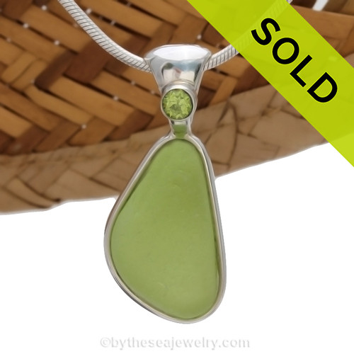 This beautiful Bright Peridot Green sea glass piece is set in our Deluxe Wire Bezel© pendant setting with a genuine Peridot gem on the solid sterling bail. Sorry this sea glass necklace pendant has been sold!