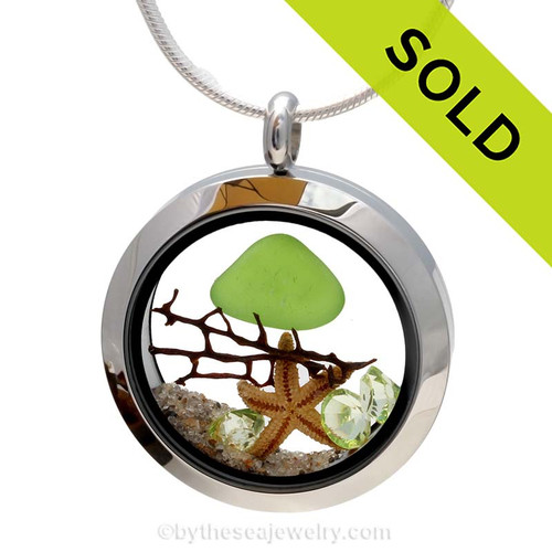 Genuine lime green sea glass piece combined with a real starfish, a bit of vintage seafan and real beach sand in this stainless steel locket. Finished with a  vivid peridot crystal gems for a bit of beachy bling. SOLD - Sorry this Sea Glass Jewelry selection is no longer available.