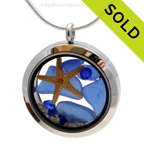 A beautiful pieces of natural blue sea glass combined in a stainless steel locket necklace with a real starfish and beach sand. Sorry this sea glass jewelry piece has been sold!