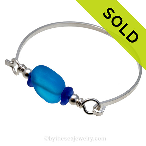 Two pieces of beach found sea glass in a blue on this solid sterling silver thin bangle sea glass bangle bracelet.  Sorry this sea glass jewelry selection has been sold!