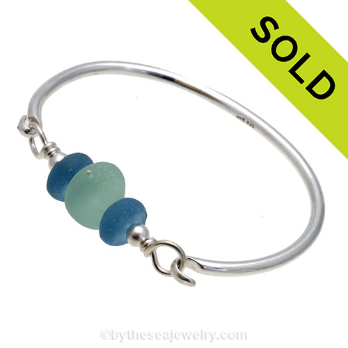 A thick and mixed seafoam green sea glass combined recycled glass beads on a full round solid sterling bangle bracelet. Sorry this sea glass bracelet has been sold!