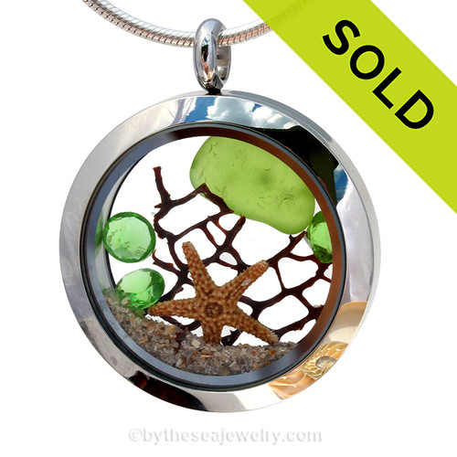 Genuine lime green sea glass piece combined with a real starfish, a bit of vintage seafan and real beach sand in this stainless steel locket. Finished with a  vivid peridot crystal gems for a bit of beachy bling.