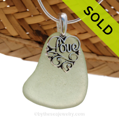 "A nice larger piece of green genuine sea glass with a solid sterling bail and detailed ""Love"" heart charm. This piece comes complete with our sterling 1MM snake chain. SOLD - Sorry this Sea Glass Necklace is NO LONGER AVAILABLE!"