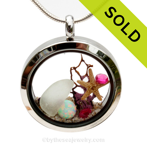 Pure white sea glass combined with a baby starfish, seafan and gems and beach sand in this twist top stainless steel locket necklace. Pink Tourmaline gem beads make this a great gift for anyone with an October Birthday!  SOLD - Sorry This Sea Glass Jewelry Selection Is NO LONGER AVAILABLE!