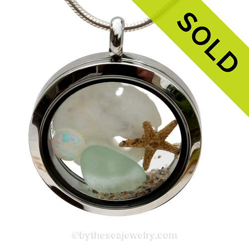 SOLD - Sorry This Sea Glass Jewelry Selection Is NO LONGER AVAILABLE! Seafoam Green sea glass combined with a baby sandollar, as simulated opal and beach sand in this twist top stainless steel locket necklace.