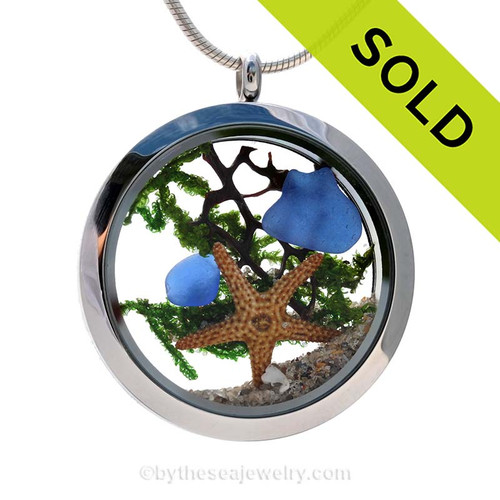"""A beautiful pieces of natural blue sea glass combined in a stainless steel locket necklace and a real starfish.. Made for ocean lovers with a bit of seafan, beach sand a bit of """"seaweed""""."""