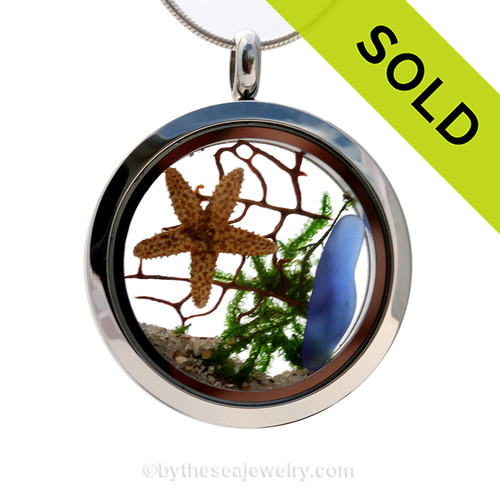 """A beautiful sliver of natural blue sea glass combined in a stainless steel locket necklace a two real starfish and beach sand. A seafan and bit of """"seaweed"""" makes this a great choice for any ocean lover! Sorry this Sea Glass Jewelry selection has been SOLD"""