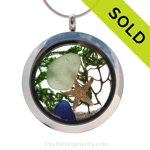 A beautiful sliver of natural blue  and seafoam green sea glass combined in a stainless steel locket necklace a real starfish and beach sand. SOLD - Sorry this Sea Glass Locket is NO LONGER AVAILABLE!