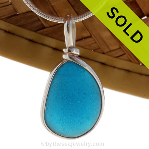 A wonderful shaped thick piece of vivid electric Aqua sea glass in our In Our Original Sterling Wire Bezel© necklace pendant. Sorry this Ultra Rare Genuine Sea Glass Jewelry piece has been SOLD!