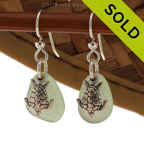 A perfect matched pair of beautiful seafoam green sea glass earrings combined with solid sterling Sea Turtle charms. A a setting that leaves much of the beauty of these natural beach found sea glass pieces shine. Sorry this Sea Glass Jewelry selection is NO LONGER AVAILABLE!