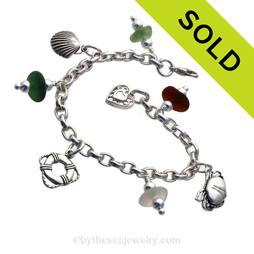 4 pieces of common color beach found sea glass combined with solid sterling nautical inspired charms in a totally solid sterling silver bracelet.
