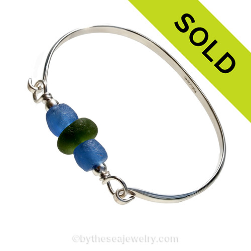 Two bright blue recycled glass beads set with a single vivid jungle green sea glass piece and sterling details on a solid sterling half round bangle bracelet.
