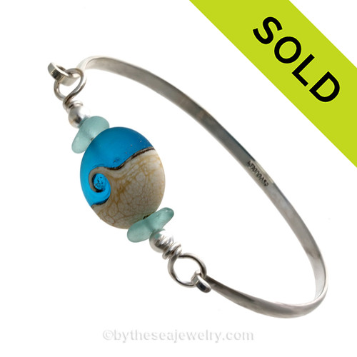 Aqua Genuine sea glass pieces set with a Vivid Blue handmade lampwork glass Wave bead set with sterling details on a solid sterling half round bangle bracelet.