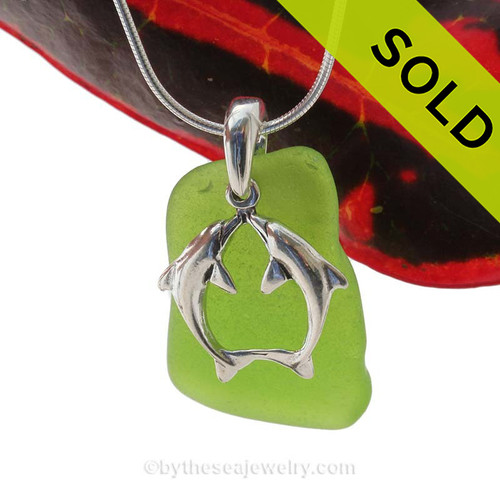 A large perfect piece of natural beach found chartreuse or lime green sea glass is combined with a solid Kissing Dolphins charm and presented on an 18 Inch solid sterling snake chain.
