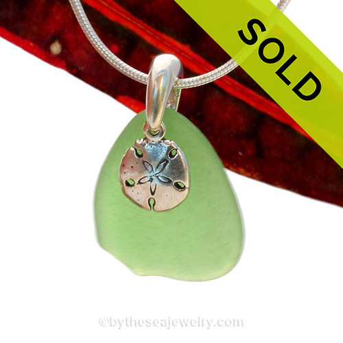 A nice piece of natural beach found vivid green sea glass is combined with a solid sandollar charm and presented on an 18 Inch solid sterling snake chain. Sorry this Sea Glass Necklace has been SOLD!