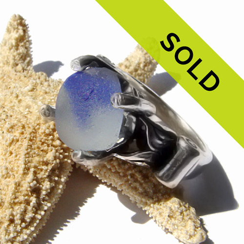 A partial blue and white sea glass marble in a sterling ring base.