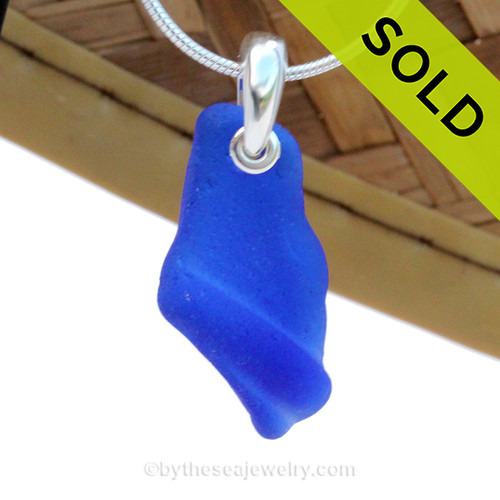 A nice curvy ridged piece of natural blue beach found sea glass necklace on a solid sterling hand cast bail. Solid Sterling professionally hand cast bail. A great piece that still bears markings of it's former life as a medicine bottle.  SOLD - Sorry this Sea Glass Necklace is NO LONGER AVAILABLE