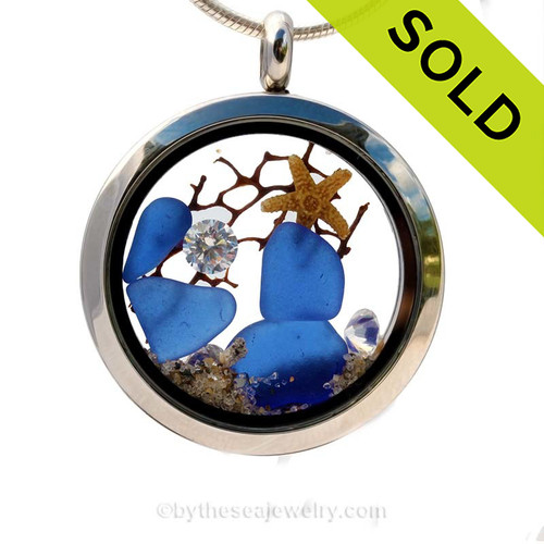 A beautiful pieces of natural blue sea glass combined in a stainless steel locket necklace with two  real starfish and beach sand. Finished with vivid CZ's that look just like diamonds. SOLD - Sorry This Sea Glass Jewerly Selection Is NO LONGER AVAILABLE!