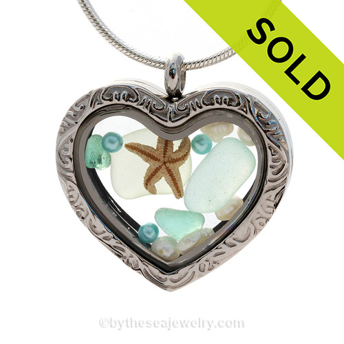 SOLD - Sorry This Sea Glass Jewelry Selection Is NO LONGER AVAILABLE! Beautiful pieces of seafoam and aqua sea glass pieces combined with a real starfish. Finished with real beach sand and pearls in this 30MM stainless steel locket.