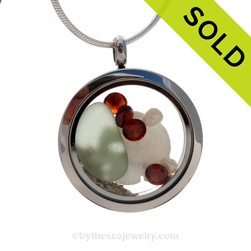 Beautiful pieces of soft Seafoam Green sea glass, a real sandollar and fresh water pearls in a stainless steel locket combined with Crystal Garnet faceted gems.