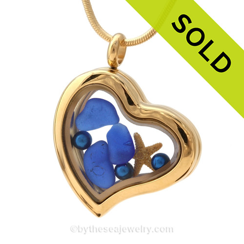 A goldtone stainless steel locket with beach found Cobalt Blue Sea Glass, a real baby starfish , finished with blue dyed pearls.