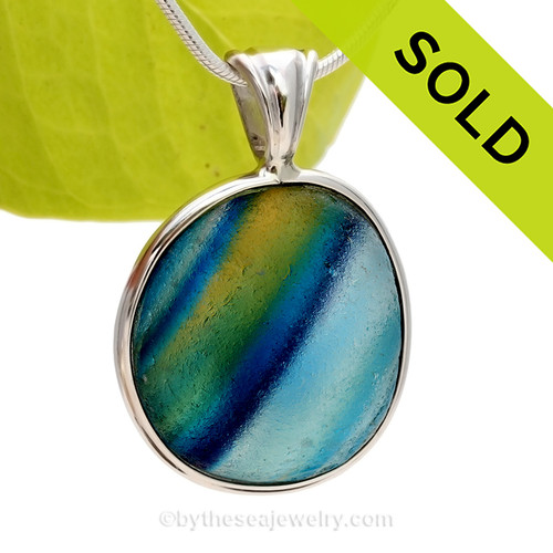 A True SUPER ULTRA ULTRA RARE Genuine Seaham Sea Glass Multi set in our Deluxe Wire Bezel© Pendant Setting.  These colors are totally natural to this type of sea glass as they were accidentally fused together over 100 years ago then tossed into the North Sea as waste. Two color sea glass pieces from this region are more common, these amazing 4+ pieces are highly prized around the world today. This piece is LARGE (SEE product details below) and not available through any other sea glass artist in the world today! Shades of Blue, Aqua, Green  Purple and Yellow are streaked inside this amazing sea glass piece. SOLD - Sorry this Ultra Rare Sea Glass Pendant is NO LONGER AVAILABLE!