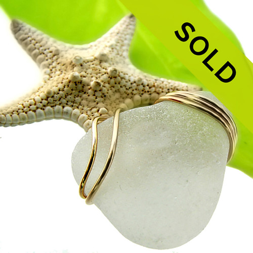 A large white sea glass necklace pendant set in a triple gold setting