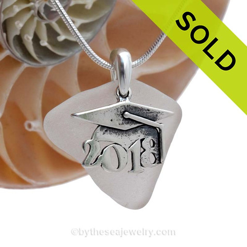 """A nice piece of white genuine sea glass with a solid sterling bail and detailed """"2018"""" graduation charm. This piece comes complete with our sterling 1MM snake chain. SOLD - Sorry this Sea Glass Necklace is NO LONGER AVAILABLE!"""