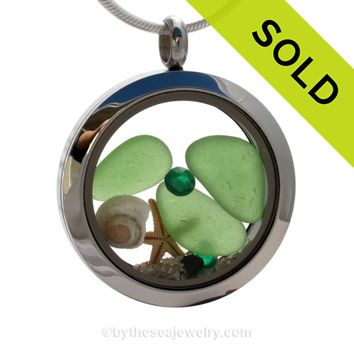 """Beautiful pieces of perfect Genuine Green Sea Glass combined with a Real Starfish and tiny nautilus shell . Finished with crystal gems in this heart locket. Emerald is the birthstone for May. Comes with a Free PLATED 18 """" Chain (not shown)."""