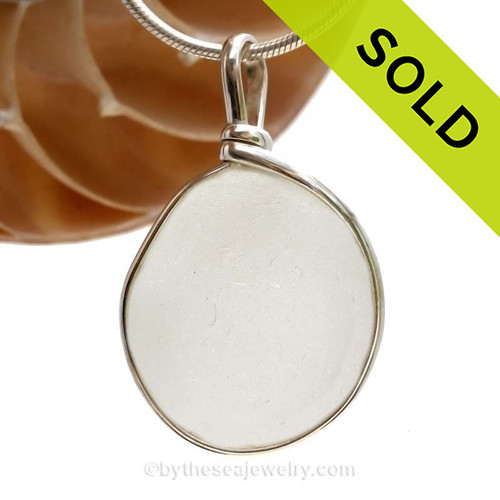 A larger and round piece of antique English Sea Glass in pure white in a solid sterling silver pendant in our Original Wire Bezel© setting. A larger well frosted piece of pure white sea glass in a naturally found shape.