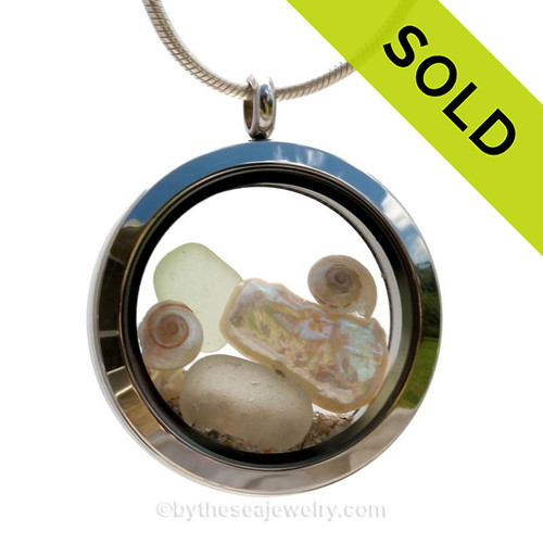 Genuine Seafoam sea glass pieces combined with a real baby sandollar, tiny pearlized nautilus shells and genuine stick pearl and real beach sand in this stainless steel locket. SOLD - Sorry this Sea Glass Locket is NO LONGER AVAILABLE!
