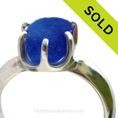 A spectacular piece of Vivid Cobalt Blue English Sea Glass set in a sturdy 6 prong Solid Sterling ring setting.  The sea glass is totally UNALTERED from the way it was found on the beach in England. It can take many hours of sorting through sea glass to find the perfect piece to fit a particular setting. SOLD - Sorry this Sea Glass Ring is NO LONGER AVAILABLE!