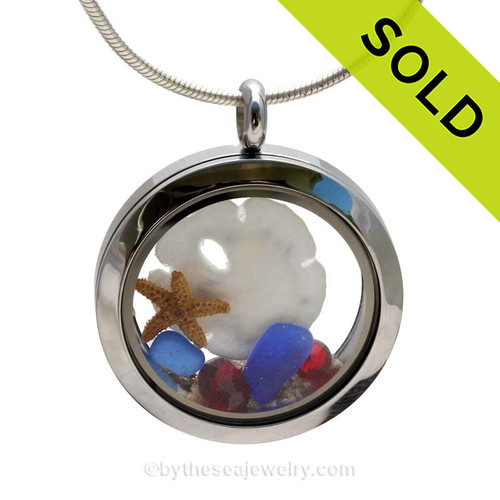 A beautiful sliver of natural blue sea glass combined in a stainless steel locket necklace a real starfish and Baby Sandollar . Vivid Ruby Gems complete the beachy look. This a great gift, specially for those with a September or July Birthday. SOLD - Sorry this Sea Glass Locket is NO LONGER AVAILABLE!