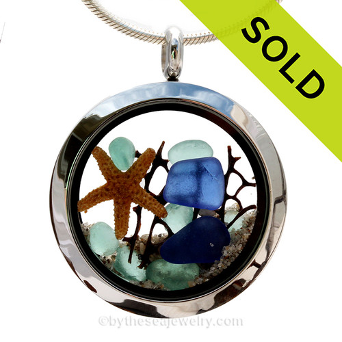 A beautiful sliver of natural cobalt blue and tiny aqua sea glass combined in a stainless steel locket necklace a real starfish and beach sand.  SOLD - Sorry this Sea Glass Locket is NO LONGER AVAILABLE!