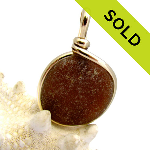 A frosty amber brown sea glass piece set in our signature 14K Rolled Gold Original Wire Bezel© setting. The sea glass piece is UNALTERED from the way it was found on the beach.! Great warm color for fall and winter! SOLD - Sorry this Sea Glass Pendant is NO LONGER AVAILABLE!