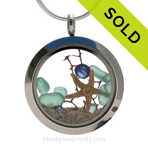 Beautiful aqua sea glass combined in a stainless steel locket necklace with a real starfish, a bit of vintage seafan and a sapphire crystal gem. Finished with real beach sand.  SOLD - Sorry this Sea Glass Locket is NO LONGER AVAILABLE!