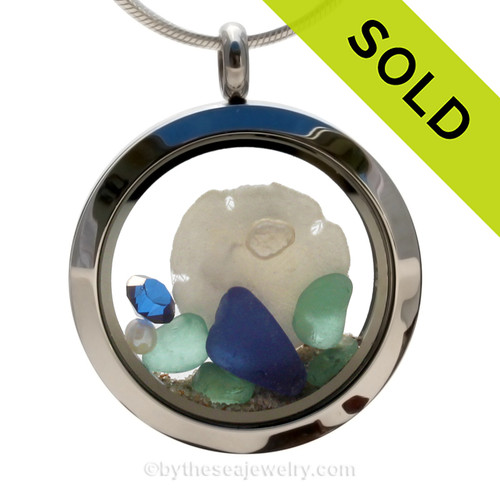 Beautiful of natural blue and Aqua sea glass combined in a stainless steel locket necklace a real Baby Sandollar . Vivid Sapphire Gems and Fresh Water Pearls complete the beachy look. SOLD - Sorry this Sea Glass Locket is NO LONGER AVAILABLE!