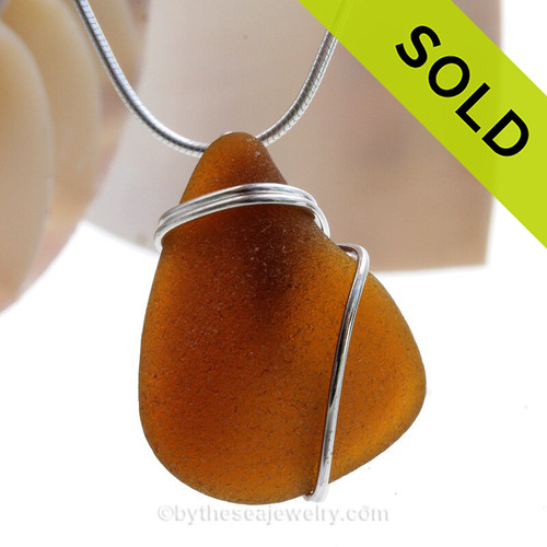 A nice piece of genuine sea glass in amber brown and a simple secure  wire wrapped sterling setting.