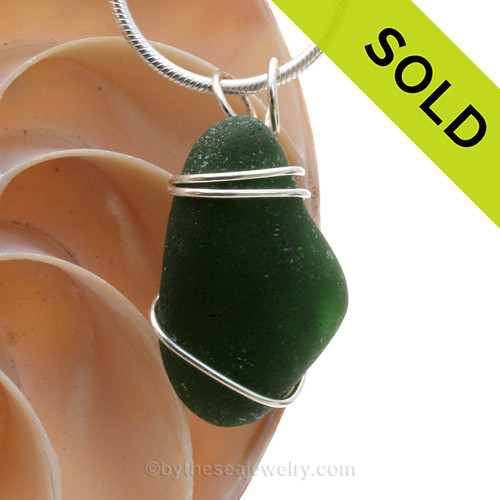 A nice piece of genuine and very thick sea glass in dark green and a simple secure  wire wrapped sterling setting.