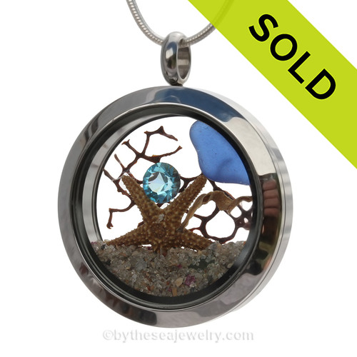 Beautiful cobalt blue sea glass combined in a stainless steel locket necklace with a real starfish, a bit of vintage seafan and a aqua crystal gem. Finished with real beach sand.  SOLD - Sorry this Sea Glass Locket is NO LONGER AVAILABLE!