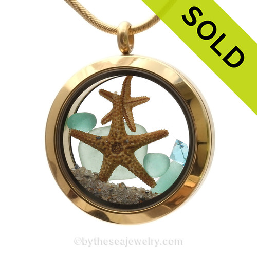 A gold tone stainless steel locket necklace with aqua found sea glass pieces and two real starfish and finished with aqua crystal gems.