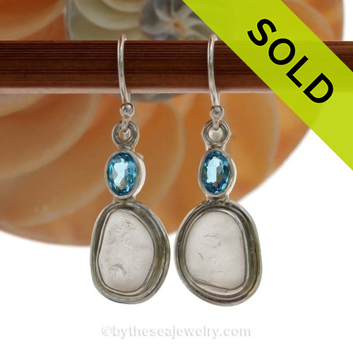 A stunning pair of pure white sea glass earrings set in a finely crafted setting in sterling silver finished with a beach bling brilliant Blue Topaz round gem.