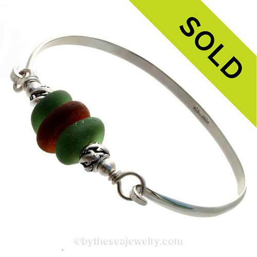 3 Pieces of Genuine Sea Glass in stunning Greens and Amber on this Solid Sterling Half Round Bangle Bracelet With Dolphin Beads.