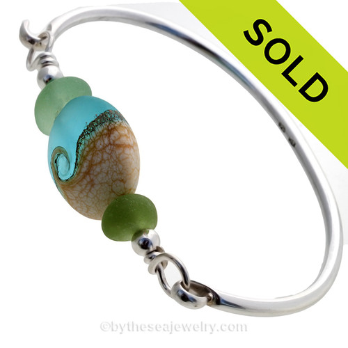 VIVID Green Genuine Sea Glass Bangle Bracelet set with a handmade lampwork glass Wave bead set with Sterling Details on a Solid Sterling Round Bangle Bracelet. This is a medium bangle at 7.5 inches.