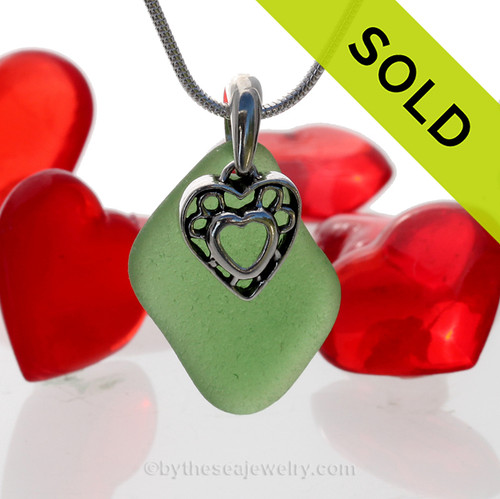 A  perfect neatly shaped bright green genuine sea glass with a solid sterling bail and detailed heart in heart charm. This piece comes complete with our sterling 1.2 MM snake chain. SOLD - Sorry this Sea Glass Necklace is NO LONGER AVAILABLE!