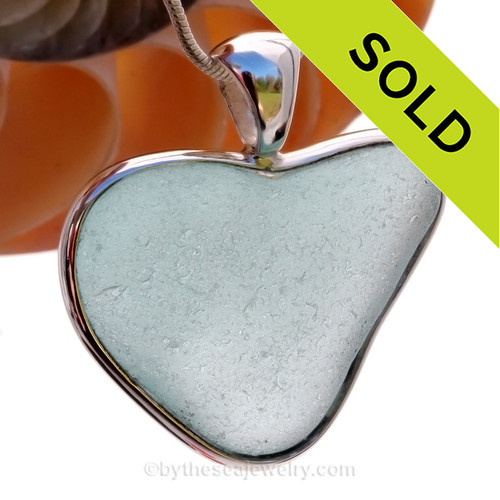 This piece features the glass and beauty of the collected seafoam sea glass and is presented on a professionally our Deluxe Wire Bezel Setting© that leaves the sea glass UNALTERED from the way it was found on the beach.Unique and rare this naturally shaped sea glass pendant is in a heart shape.