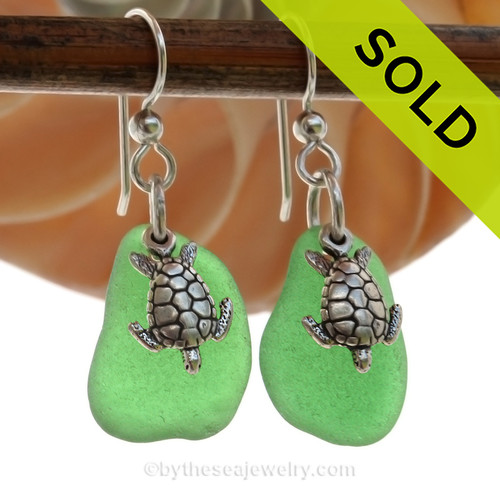 Natural beach found green sea glass pieces are set with solid sterling Sea Turtle charms and are presented on sterling silver fishook earrings.