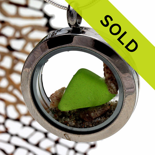 Beautiful small piece of vivid lime green sea glass combined with a small shells and beach sand in a stainless steel locket. Sorry this locket has been sold!