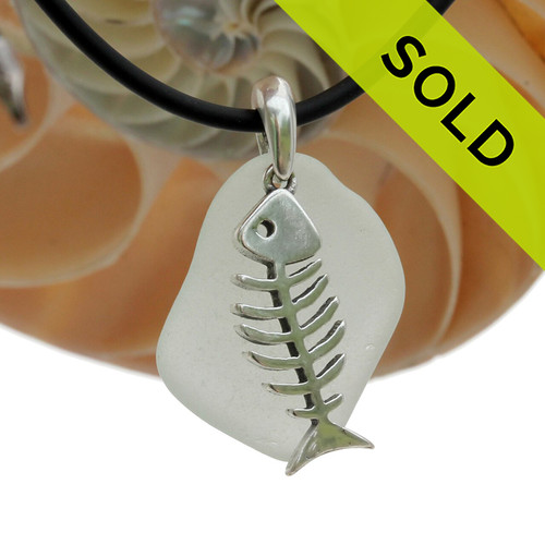 A nice piece of Sea Green Natural Sea Glass Necklace Set On Silver Bail With Black Neoprene Cord with sterling clasps and finished with a solid sterling Fish Bones Charm.